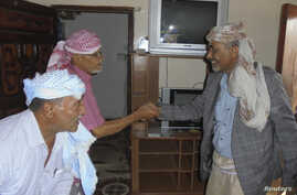 Yemen's Defence Minister General Mahmoud al-Subaihi, right, shakes hands with visitors in his home in Yemen's southern province of Lahej, where he fled from the capital, Sana'a, March 8, 2015.