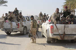 Shi'ite fighters and Iraqi army members ride in vehicles during a patrol in Jurf al-Sakhar, Oct. 25, 2014.