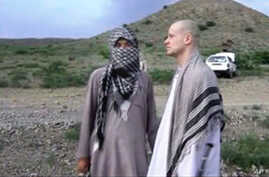 FILE: In this image taken from video obtained from Voice of Jihad website on June 4, 2014, Sgt. Bowe Bergdahl, right, stands with a Taliban fighter in eastern Afghanistan.