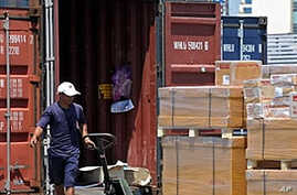 A Thai worker loads boxes into an export container at the Port Authority in Bangkok (File)