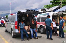 Ambulance workers wait to transport the bodies of the victims of the crashed Trigana Air Service flight at Sentani airport in Jayapura, Papua province, Indonesia, Aug. 18, 2015.