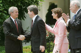 FILE - President George W. Bush shakes hands with newly sworn-in Judge on the U.S. Court of Appeals for the District of Columbia Brett Kavanaugh in the Rose Garden of the White House, June 1, 2006.
