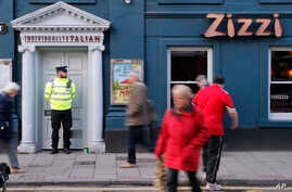 """Police outside an Italian restaurant in Salisbury, England, Tuesday March 6, 2018, near to where former Russian spy double agent Sergei Skripal and his companion were found critically ill Sunday following exposure to an """"unknown substance"""". 66-year o"""