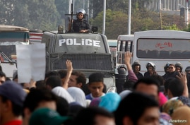 Protesters gesture with four fingers after blocking Al Nasr street in front of Al-Azhar University headquarters at Cairo's Nasr City district, Nov. 19, 2013.