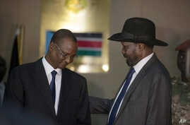South Sudan's First Vice President Taban Deng Gai, left, speaks with President Salva Kiir, right, after Taban was sworn in, replacing opposition leader Riek Machar, at the presidential palace in Juba, South Sudan, Tuesday, July 26, 2016.