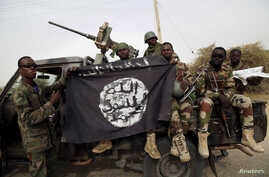 FILE - Nigerian soldiers hold up a Boko Haram flag that they had seized in the retaken town of Damasak, Nigeria, March 18, 2015.