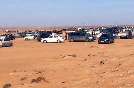 Displaced Libyans from the western city of Tawergha wait by their cars to enter the city, which lies about 250 kilometres east of the capital Tripoli, on Feb. 1, 2018,