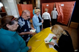 People wait in line at a polling station in the center of Slovyansk, eastern Ukraine, May 11, 2014.