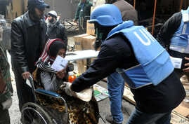 This photo released by the Syrian official news agency SANA shows a U.N relief worker giving food supplies to a Palestinian woman in a wheelchair at the gate of the besieged Yarmouk refugee camp on the southern edge of Damascus, Feb. 4, 2014.
