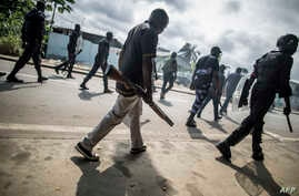 Gabonese police forces patrol as they clear barricades in the streets adjacent to the National Assembly, in Libreville, Sept. 1, 2016.