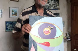 FILE - Pierre Pol Vincke poses with a painting by his daughter, Edith, in Ramillies, Belgium, June 26, 2017. Belgium is one of few countries that allow euthanasia but doctors refused his daughter's request despite years of psychiatric illness, and Ed...