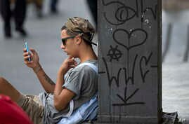 FILE - A youth checks his cell phone in Sao Paulo, Brazil.
