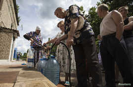 Residents collect water at a pumping station in the eastern Ukranian city of Slaviansk, June 17, 2014. Slaviansk, the pro-Russian separatist stronghold, is faced with ongoing shortages, utility outages and frequent artillery fire.