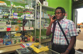 FILE - Prominent gay rights activist and Sexual Minorities Uganda program coordinator Pepe Julian Onziema makes a phone call while in a pharmacy in the suburbs of Kampala, Uganda, Feb. 26, 2014.