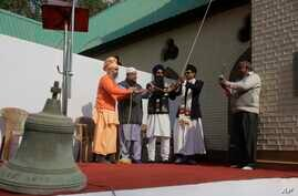 An old bell that was removed is seen in foreground as people from various faiths including Muslims, Hindus and Sikhs ring the new bell during its installation at the Holy Family Catholic Church in Srinagar, Indian controlled Kashmir, Oct. 29, 2017.