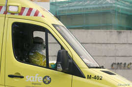 An ambulance driver in protective suit arrives at Madrid's Carlos III Hospital carrying a possible new Ebola patient, in Madrid, Oct. 16, 2014.