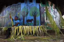 FILE - A Sarayaku Indian man creates decorations out of palms in the village of Sarayaku in Ecuador.