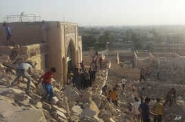 FILE - FILE - In this July 24, 2014 file photo, people walk on the rubble of the destroyed Mosque of The Prophet Younis, or Jonah, in Mosul, 225 miles (360 kilometers) northwest of Baghdad, Iraq.
