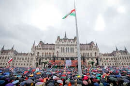 Supporters wait in the rain for Hungarian Prime Minister Viktor Orban's speech outside the Hungarian Parliament building in Budapest, Hungary, March 15, 2018, during celebrations of the Hungarian national holiday.
