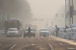 Pedestrians cross a road amid smog on a polluted day in Nanjing, Jiangsu province, China, Jan. 30, 2018.