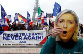 """A person holds a mask of France's National Front (FN) defeated presidential candidate, Marine Le Pen, as people gather with French and European flags near the Eiffel Tower and a banner with the message, """"France tells Hate: Never Again"""" the day after ..."""
