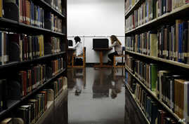 """FILE - Students are seen studying in a library on the campus of California State University in Long Beach, California, Oct. 19, 2012. Advocates of the """"gap year"""" say it helps young people gain experiences they cannot learn from books."""