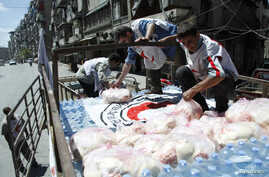 Syrian Arab Red Crescent members place a red crescent flag on top of a food aid truck before moving it to Aleppo Central Prison, May 11, 2014.