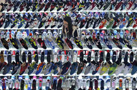 A customer shops for shoes at a mall in Hefei, Anhui province, March 10, 2015. China's annual consumer inflation recovered in February, exceeding expectations, but producer prices continued to slide, underscoring deepening weakness in the economy and