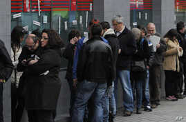 People wait outside an unemployment office in Madrid, Spain, Apr. 2, 2013.