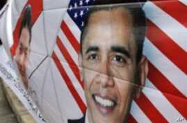 A man holds a banner depicting US President Barack Obama during a pro-Obama rally in Jakarta, 19 Mar 2010