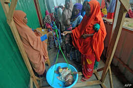 FILE - Newly displaced Somali women weigh their malnourished children as they try to receive medical treatment on the outskirts of Mogadishu, Somalia, on April 11, 2017.