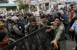 FILE - Police officers set up a roadblock on the outskirts of Phnom Penh, Cambodia, May 30, 2016, ahead of an opposition protest. Having dissolved the country's main opposition party, authorities are now moving against a human rights NGO.