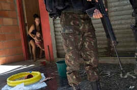 A woman moves her baby inside while a soldier patrols during an operation at the Rocinha slum, in Rio de Janeiro, Brazil, Oct. 10, 2017.