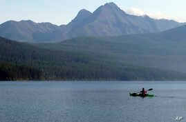 FILE - A woman kayaks on Kintla Lake in Glacier National Park, Mont. A grizzly bear attacked and killed a 38-year-old mountain biker Wednesday, June 29, 2016.