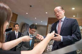 Chinese Ambassador to the UN and current Security Council President Liu Jieyi, right, speaks to reporters during a break in a Security Council meeting on the situation in the Middle East, including the Palestinian question,  July 25, 2017 at United N