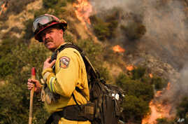 A crew member with California Department of Forestry and Fire Protection (Cal Fire) battles a brushfire on the hillside in Burbank, Calif., Saturday, Sept. 2, 2017.