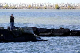 FILE - A man fishes from a break wall on the shores of Lake Erie, Oct. 16, 2017, in Cleveland.