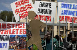 Athletes holds banners and look through the locked the gate at the Kenya Athletic offices in Nairobi, Kenya, Monday, Nov. 23, 2015.