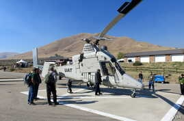 """Federal firefighting managers peruse the """"optionally piloted"""" K-MAX helicopter at the Lucky Peak Helibase in Idaho. (Credit: Tom Banse)"""