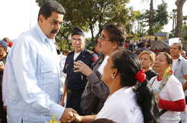 Venezuela's President Nicolas Maduro (L) talks with supporters during a mass at Miraflores Palace in Caracas, in this handout picture provided by Miraflores Palace on April 11, 2016.