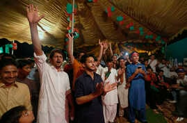 Supporters of Pakistani politician Imran Khan, chief of Pakistan Tehreek-e-Insaf party, celebrate projected unofficial results announced by television channels indicating their candidates' success in the parliamentary elections in Islamabad, Pakistan