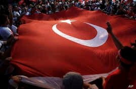 Protestors wave a large Turkish flag during an anti coup rally in Taksim square in Istanbul, July 25, 2016.
