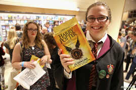 """A woman holds copies of the book from the play of """"Harry Potter and the Cursed Child"""" parts One and Two at a bookstore in London, July 31, 2016."""