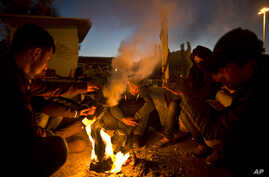Afghan refugees gather around a fire to warm themselves in the early hours while waiting to get on board a ferry traveling to Athens, at the port of Mitylene on the northeast Greek island of Lesbos, Oct. 9, 2015.