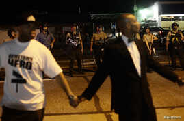 Civilian peacekeepers join hands to separate demonstrators protesting against the shooting of Michael Brown away from the police in Ferguson, Missouri, Aug. 19, 2014.