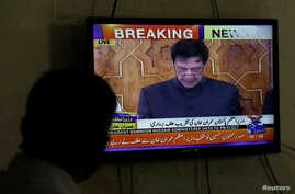 A man looks at a television screen displaying cricketer-turned-politician Imran Khan being sworn in as prime minister of Pakistan, in Karachi, Pakistan, Aug. 18, 2018.