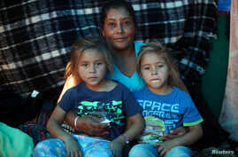 Maria Lila Meza, a 39-year-old migrant woman from Honduras, part of a caravan of thousands from Central America trying to reach the U.S., sits with her five-year-old twin daughters Cheili Nalleli Mejia Meza and Saira Nalleli Mejia Meza inside their t...