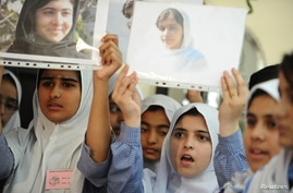 Students hold pictures of schoolgirl Malala Yousufzai, who was shot by the Taliban, during a tribute at the Pakistani Embassy in Abu Dhabi October 15, 2012.