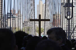 FILE - A replica cross rises above the crowd during a procession across the Brooklyn Bridge in New York, April 6, 2012. The Diocese of Brooklyn reached a $27.5 million settlement with four men who said they were sexually abused as boys.
