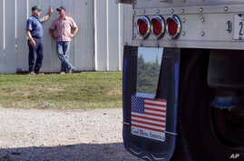 FILE - In this July 12, 2018 photo, farmer Don Bloss, left, talks to his son Mark behind a grain truck on his farm in Pawnee City, Neb.